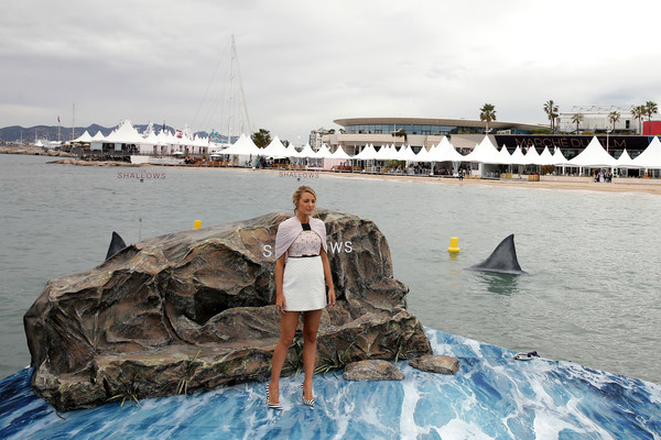 Blake Lively hanging out on a fake rock with fake sharks