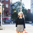 In preppy school girl style with a plaid skirt and knee-high socks.
