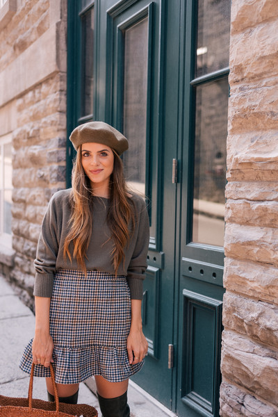 In gray with a plaid skirt and thigh-high boots.
